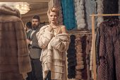 Fur Coat, Sensual Woman With Man In Shop. Fur Coat, Couple In Love, Shopping. poster