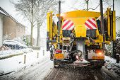 Winter service truck or spreading salt and sand on the road surface to prevent icing poster