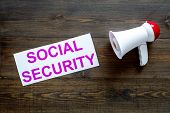 Social Security Concept. Printed Words Social Security Near Megaphone On Dark Wooden Background Top  poster
