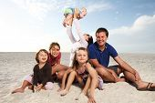 picture of family fun  - Beautiful family enjoying sunny day at the beach - JPG