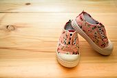 Childs Textile Sneakers White Lace Shoes On Wooden Floor Background Empty Space. poster