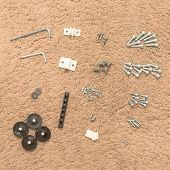 Furniture Assembly Tools And Screw Nuts On Rough Carpet Background poster