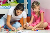 Mom And Daughter Sitting On The Floor In The Nursery And Crafting Crafts poster