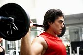 stock photo of muscle man  - man lifting weights at the gym looking serious - JPG