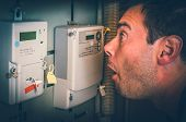 Terrified Man Is Checking Electricity Meter - Consumption And Expensive Electricity Concept - Retro  poster