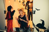 Halloween Dresses On Mother And Son And Witch Costumes And Witch Hats. Background Decorated For Hall poster