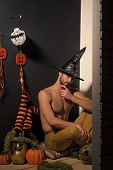 Halloween An And Pumpkins, Stockings, Ghost On Black Wall. Macho In Witch Hat And Bared Torso Sittin poster