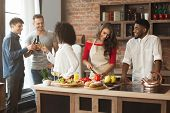 Group Of Multiracial Friends Cheering While Cooking Dinner At Kitchen. poster