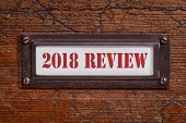 2018 review - a label on grunge wooden file cabinet. A passing year summary and review concept. poster