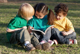 foto of children group  - Group of children with the book on a grass in park - JPG
