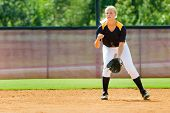 stock photo of fastpitch  - Young teen girl playing softball in organized game - JPG