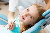 picture of cavities  - Little girl sitting in the dentists office - JPG