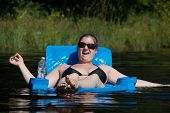 stock photo of painted toenails  - Smiling young woman with sunglasses lounging in blue floating chair in lake with painted toenails and a bottle of water - JPG