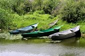 stock photo of boggy  - Several fishing boats on the shore near the boggy lake - JPG