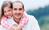 stock photo of family bonding  - Portrait of a happy father and daughter smiling outdoors - JPG