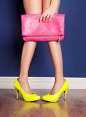 stock photo of pink shoes  - Girl wearing high heels and holding a bag - JPG