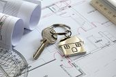 stock photo of blueprints  - House keys on a house plan blueprint concept for new house design or home improvement - JPG