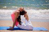 pic of arch foot  - Young woman arching her back and touching her head with her feet for a yoga pose at the beach - JPG