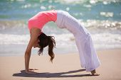 image of arch foot  - Beautiful young woman arching her back and standing backwards on hands and feet while doing yoga at the beach - JPG