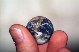 pic of megalomania  - two fingers holding planet earth; earth is marble size.  ** Note: Slight graininess, best at smaller sizes - JPG