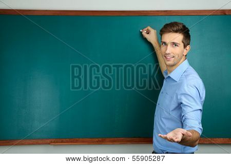 Young teacher near chalkboard in school classroom poster