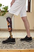 stock photo of artificial limb  - Male prosthesis wearer learning to transfer his weight on uneven surfaces in a special parcour or interior area where surfaces have been laid out to simulate realistic environmental situations - JPG