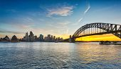 stock photo of cbd  - Dramatic widescreen panoramic image of the city of Sydney at sunset including the Rocks Bridge Opera House and a broad view of CBD and the water in the harbour - JPG