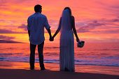 Just married couple holding hands on the beach at sunset, Hawaii Beach Wedding