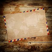 stock photo of manila paper  - vintage postcard with envelop on wooden background - JPG