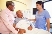 stock photo of geriatric  - Nurse Talking To Senior Couple In Hospital Room - JPG