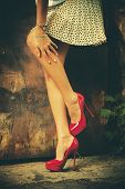 pic of short skirt  - woman legs in red high heel shoes and short skirt outdoor shot against old metal door - JPG