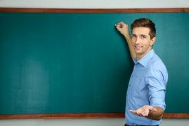 pic of classroom  - Young teacher near chalkboard in school classroom - JPG