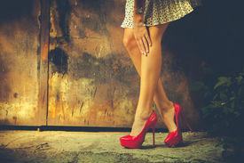 stock photo of short legs  - woman legs in red high heel shoes and short skirt outdoor shot against old metal door - JPG