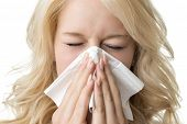 foto of sneezing  - Portrait of a ill blond woman who is sneezing in a tissue - JPG