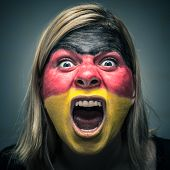picture of horrifying  - Portrait of angry woman with flag of Germany painted on face - JPG