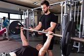 stock photo of personal assistant  - Bench press weightlifting man with personal trainer in fitness gym - JPG