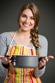 picture of saucepan  - Portrait of cheerful housewife in apron holding saucepan - JPG