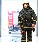 pic of firefighter  - Young firefighter against truck in firefighting depot  - JPG