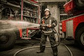 picture of firefighter  - Firefighter holding water hose near truck with equipment - JPG