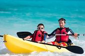 foto of canoe boat man  - Father and son kayaking at tropical ocean - JPG