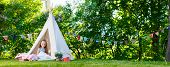 foto of tipi  - Adorable little girl having fun playing outdoors on summer day - JPG