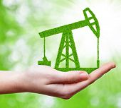stock photo of hand drill  - Green oil pump in hand - JPG