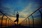 pic of slender  - silhouette of a slender woman doing yoga on the sea with sunrise - JPG