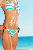 image of sun tan lotion  - Close up of tanned cute woman standing on the beach in blue striped swim wear and cute drawing of sun on her belly made of sunscreen cream
