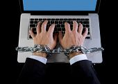 picture of addiction  - Hands of caucasian businessman addicted to work tied and bond with iron chain handcuffed to computer laptop in workaholic internet slave and addict concept - JPG