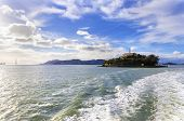 stock photo of alcatraz  - The Alcatraz Penitentiary now a museum and the Golden Gate bridge in San Francisco California United States of America viewed from the coast on a sunny day.
