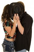 image of sneak  - A man and woman sneaking a kiss behind a western hat - JPG