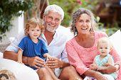 pic of grandparent child  - Portrait Of Grandparents Sitting Outdoors With Grandchildren - JPG
