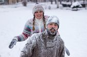 image of snowball-fight  - Cute young hipster couple covered in snow in the middle of a snowball fight - JPG