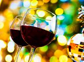 stock photo of sparkling wine  - two red wine glasses against colorful bokeh lights and sparkling disco ball background festive and fun concept - JPG
